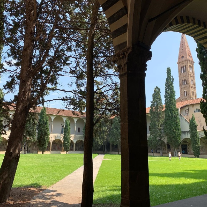 A photo of one of Santa Maria Novella's interior grassy cloisters, with its tower visible above the rooftop.
